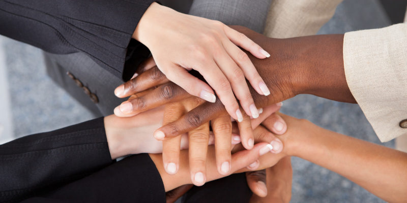 21477410 - high angle view of multiracial businesspeople stacking hands over each other